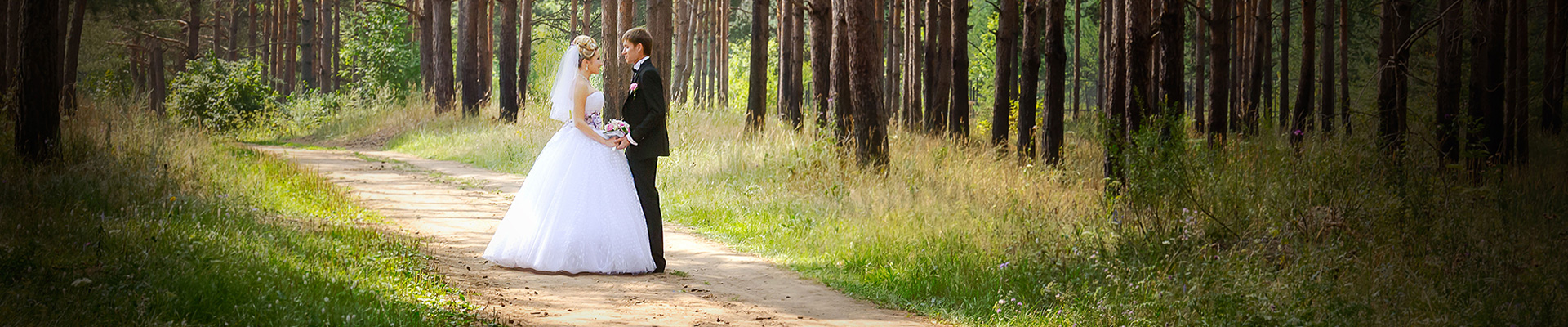 image of newly married couple on a forest path